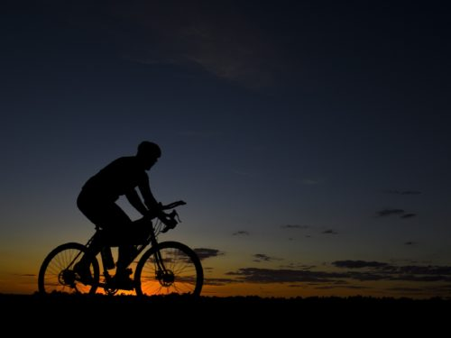 A biker is silhouetted against the soft dawn light near our Lander hotel
